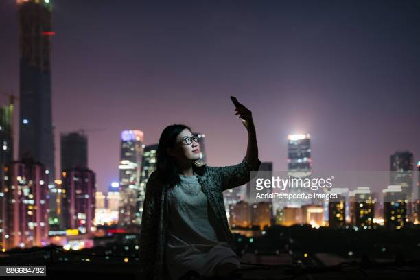 Woman Taking Selfies on rooftop at Night
