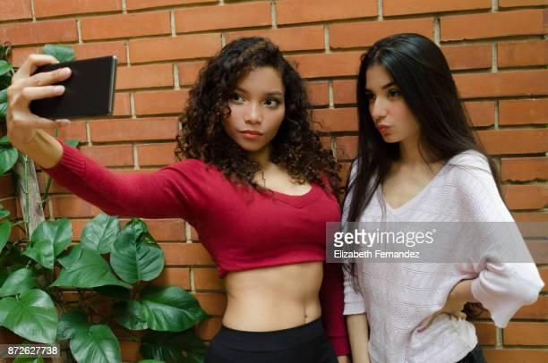 woman taking self-portrait with their camera phone - photo messaging - fotografias e filmes do acervo