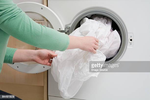 woman taking sheet from washing machine - sheet bedding stock pictures, royalty-free photos & images