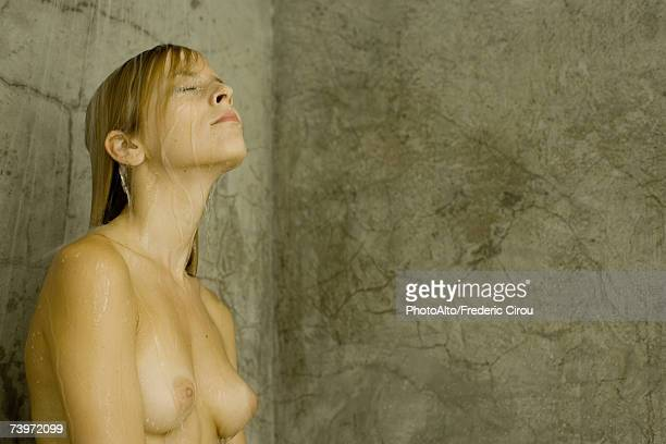 Woman taking shower, chest up