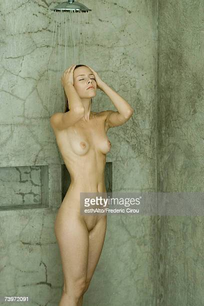 Woman taking shower, eyes closed, three quarter length