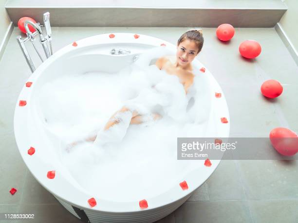 Woman taking shower in honeymoon hot tub suite