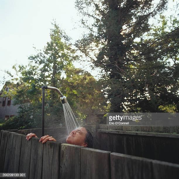 woman taking shower outdoors - frau unter dusche stock-fotos und bilder