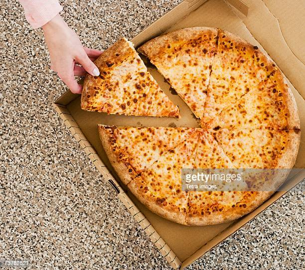 woman taking slice of pizza from box - pizza box stock photos and pictures