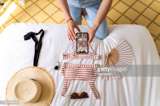 woman taking smartphone picture of bikini on bed - selling stock pictures, royalty-free photos & images