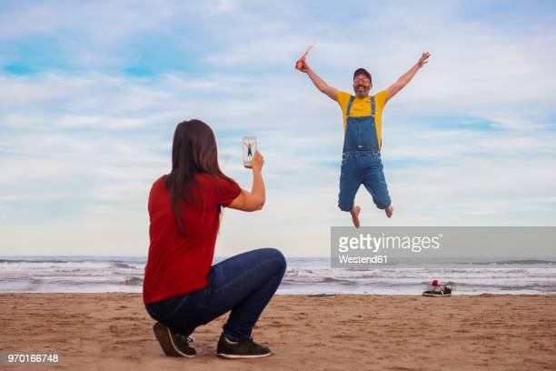 Woman taking smartphone picture of happy man  jumping on the beach