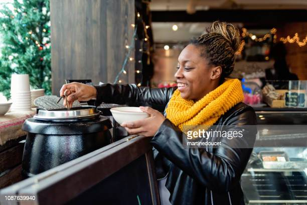 Woman taking soup in self service restaurant in winter.
