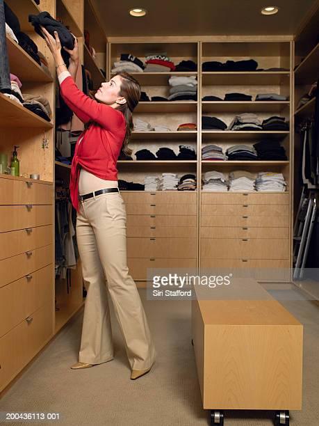 Woman taking sweater off shelf in walk-in closet