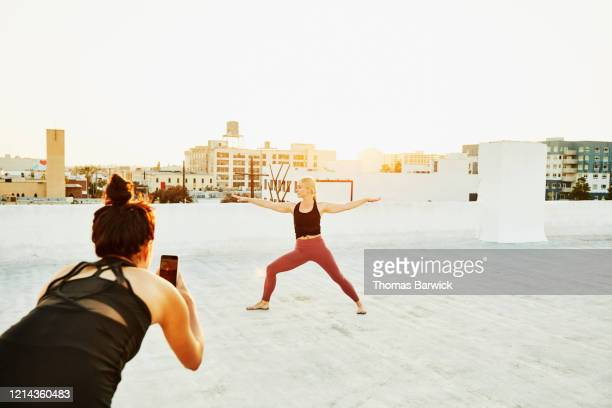 woman taking video of friend doing yoga on rooftop at sunset - shooting photo photos et images de collection
