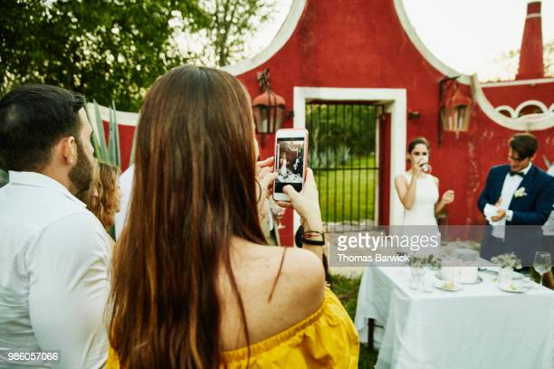 Woman taking video with smartphone of bride and groom cutting cake during outdoor wedding reception