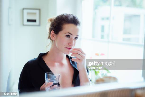 woman taking vitamins and supplements. - nutritional supplement stock pictures, royalty-free photos & images
