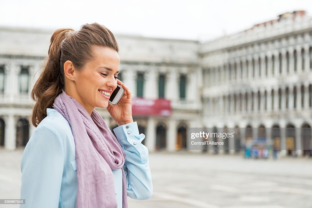 Woman talking cell phone on piazza san marco in venice : Stock Photo