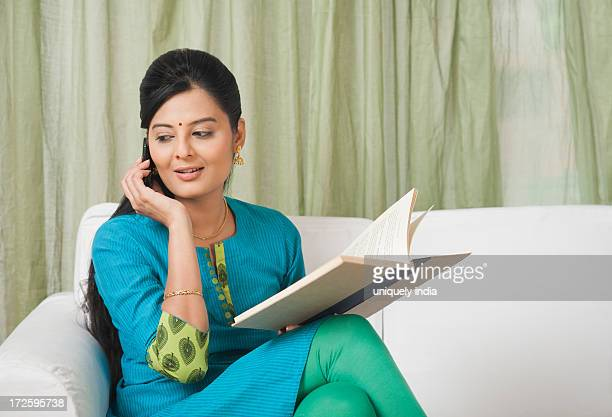 woman talking on a mobile phone while holding a book - salwar kameez stock photos and pictures