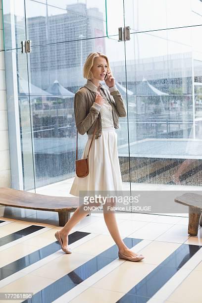 woman talking on a mobile phone while walking on an airport - sac à main en cuir photos et images de collection