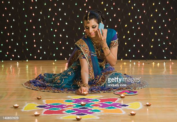 Woman talking on a mobile phone with decorating oil lamps near rangoli