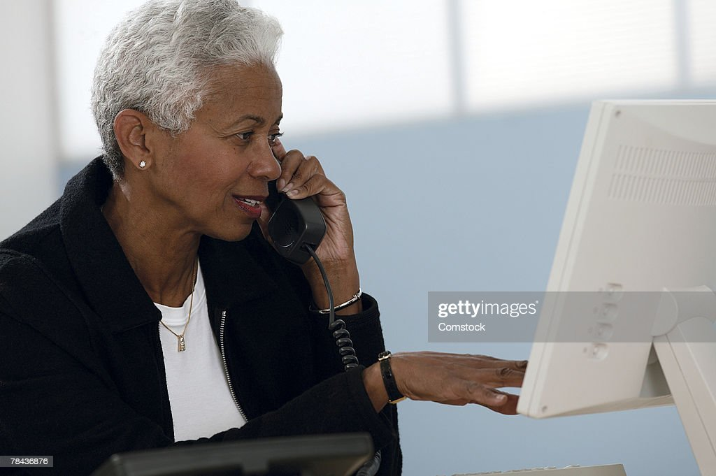 Woman talking on cell phone and using computer : Stockfoto