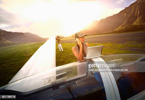 Woman talking on cell phone at glider airplane