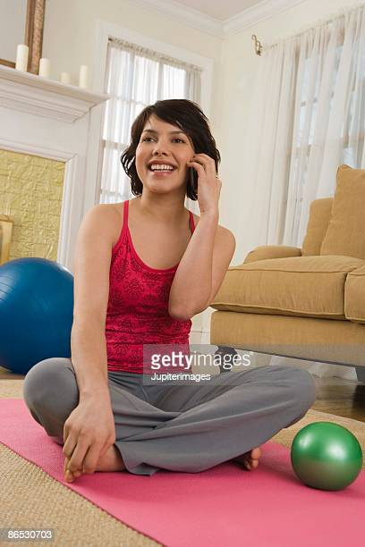 Woman talking on cell phone on yoga mat