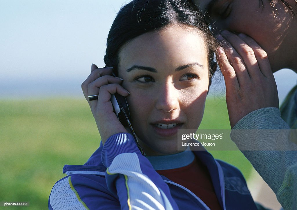 Woman talking on cell phone with man whispering in her ear, close up. : Stockfoto