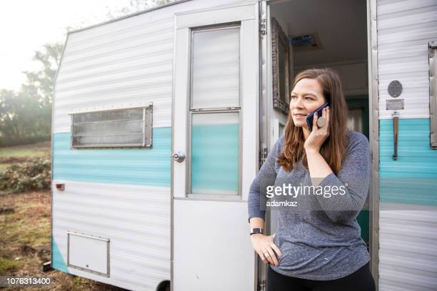 Woman Talking on Cellphone at Camping Trailer