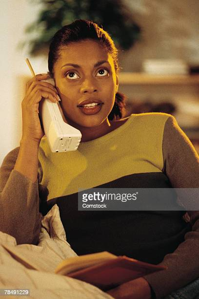 Woman talking on cordless telephone and reading book