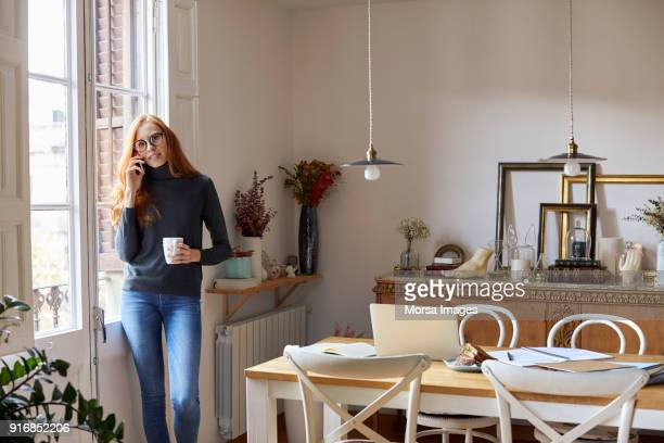 woman talking on mobile phone by window at home - hygge stock pictures, royalty-free photos & images