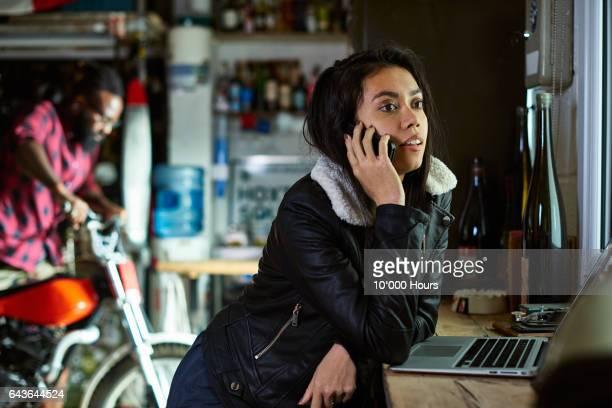 Woman talking on mobile phone in workshop.