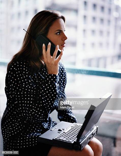 Woman talking on mobile phone, laptop resting on lap