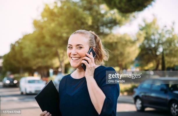 woman talking on mobile phone on the street - cris cantón photography fotografías e imágenes de stock