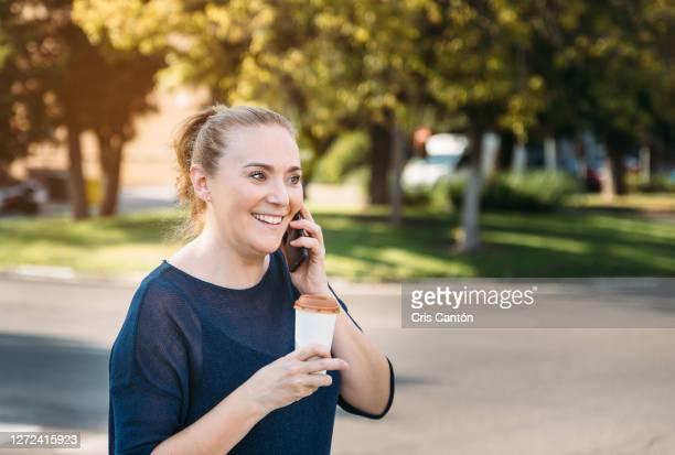 woman talking on mobile phone outdoors - cris cantón photography fotografías e imágenes de stock