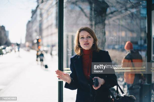 Woman talking on mobile phone through headphones while waiting at bus stop in city during sunny day