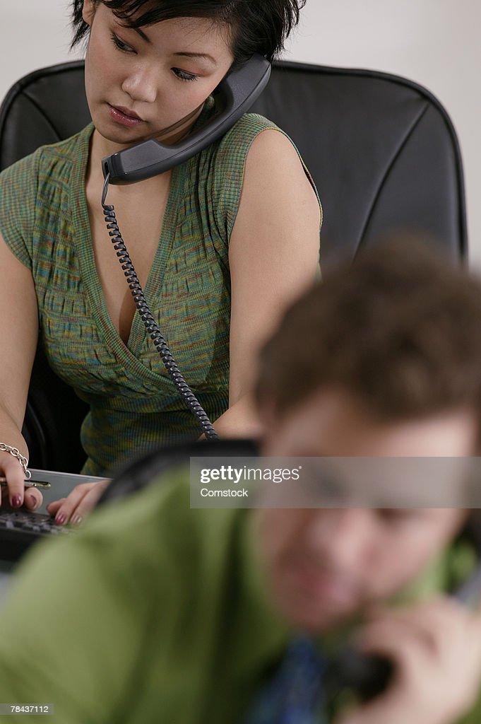 Woman talking on phone among co-worker : Stockfoto