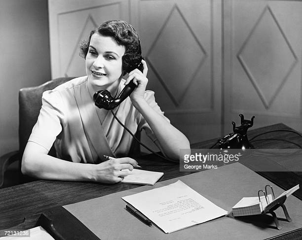 Woman talking on phone at desk (B&W)
