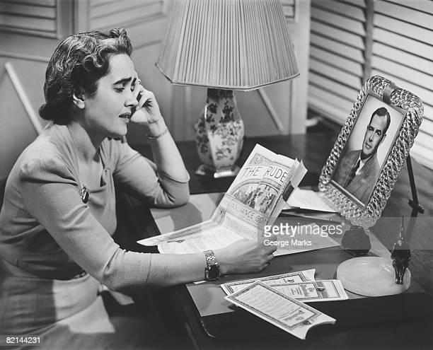 Woman talking on phone at desk, (B&W)