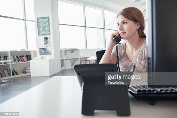 Woman talking on phone in business office