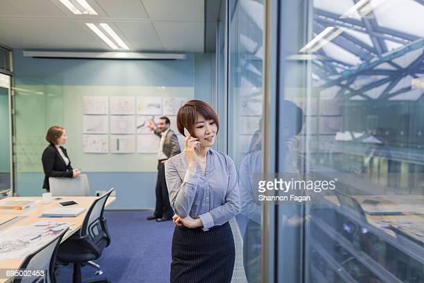 Woman talking on phone in design meeting room