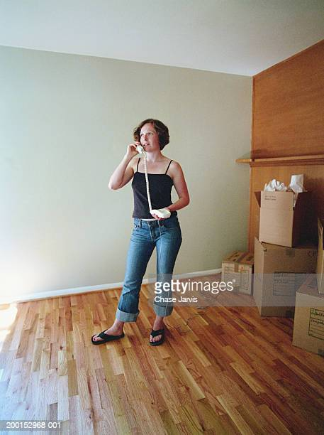 Woman talking on phone in empty room, moving boxes against wall