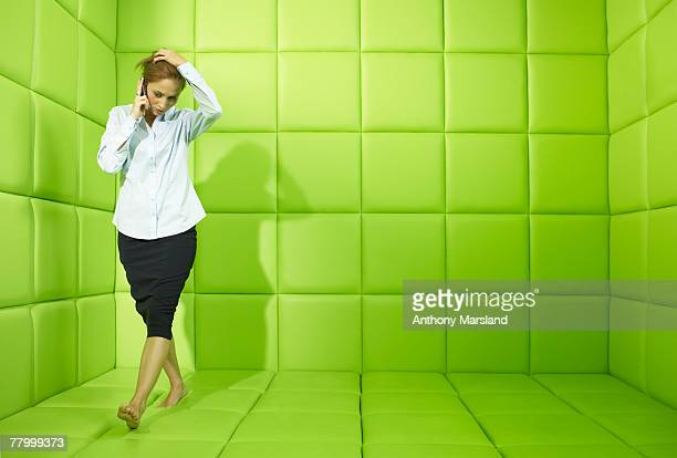 Woman talking on phone in green padded cell