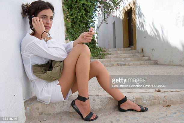 Woman talking on phone, leaning on wall