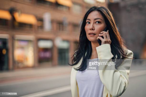 woman talking on phone - yellow blazer stock photos and pictures