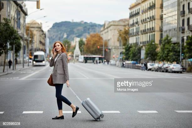 Frau am Telefon zu Fuß mit Gepäck