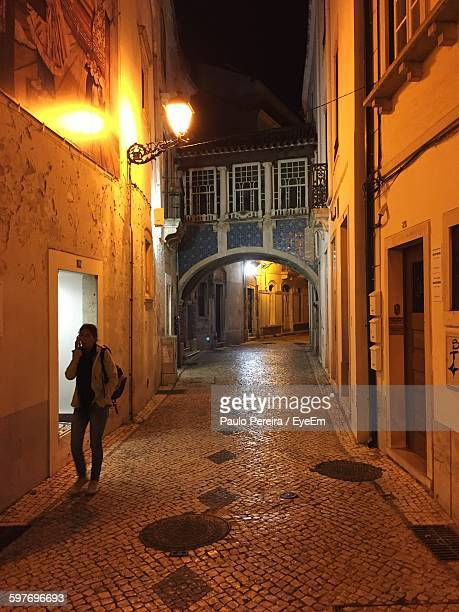woman talking on phone while walking in alley amidst buildings - leiria district stock photos and pictures