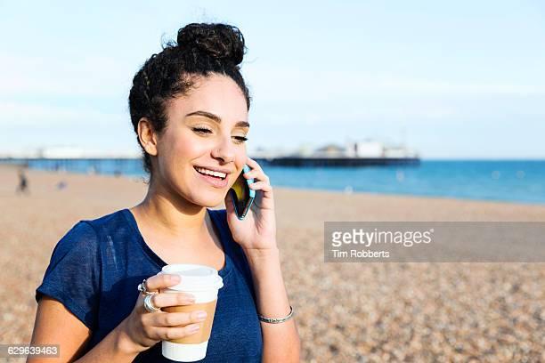 Woman talking on smart phone on beach