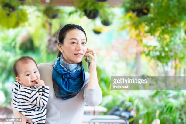 woman talking on smartphone with holding baby - 30代の女性 ストックフォトと画像