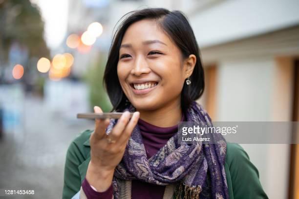 woman talking on speaker phone walking in the city - koreanischer abstammung stock-fotos und bilder
