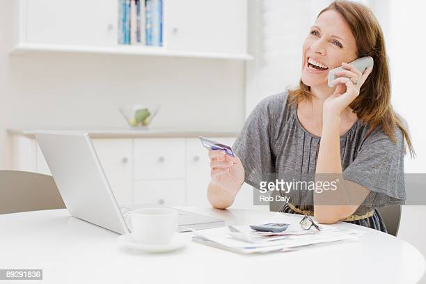 Woman talking on telephone and holding credit card