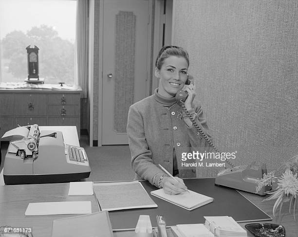 woman talking on telephone and writing - {{relatedsearchurl(carousel.phrase)}} imagens e fotografias de stock