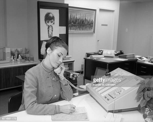 woman talking on telephone and writing - {{ contactusnotification.cta }} stock pictures, royalty-free photos & images