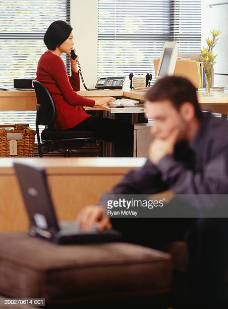 Woman talking on telephone and young man using laptop, in office, side view