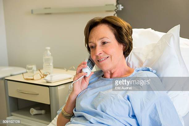 Woman talking on telephone in hospital bed